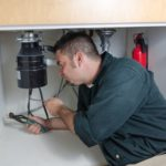 a-plumber-laying-under-a-house-hold-sink-working-on-a-garbage-disposal