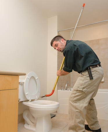 Plumber with auger in clogged toilet