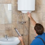 male-plumber-holding-clipboard-checking-electric-boiler