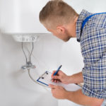 plumber-with-clipboard-in-front-of-electric-boiler
